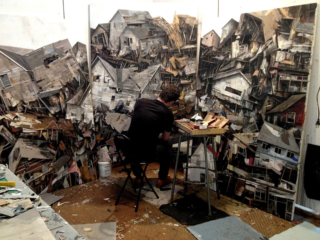 A man painting fragmented houses on a wall